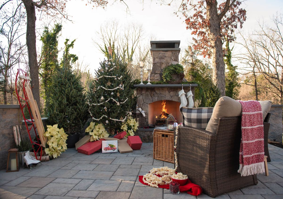 Backyard patio decorated for the holidays with a stone fire place and mantel.