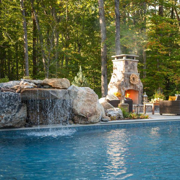 Stone waterfall atop the underground installed fiberglass pool
