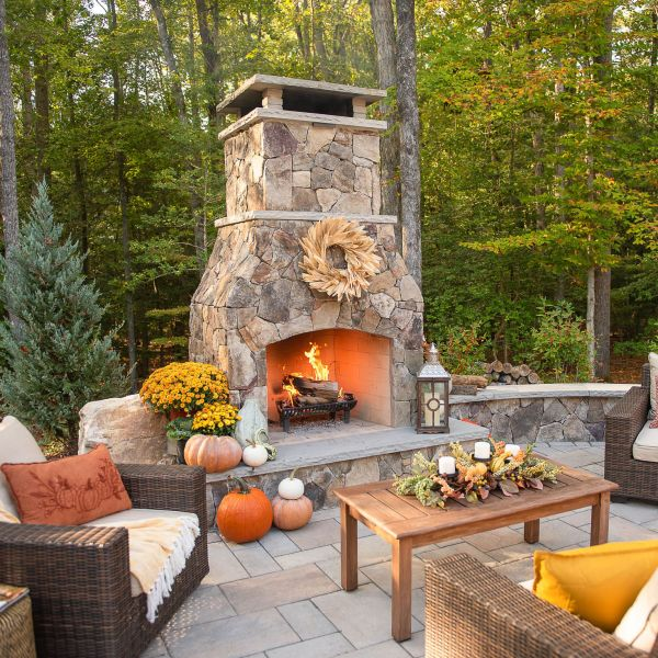 classic high-end fireplace installed into backyard patio with large hearth