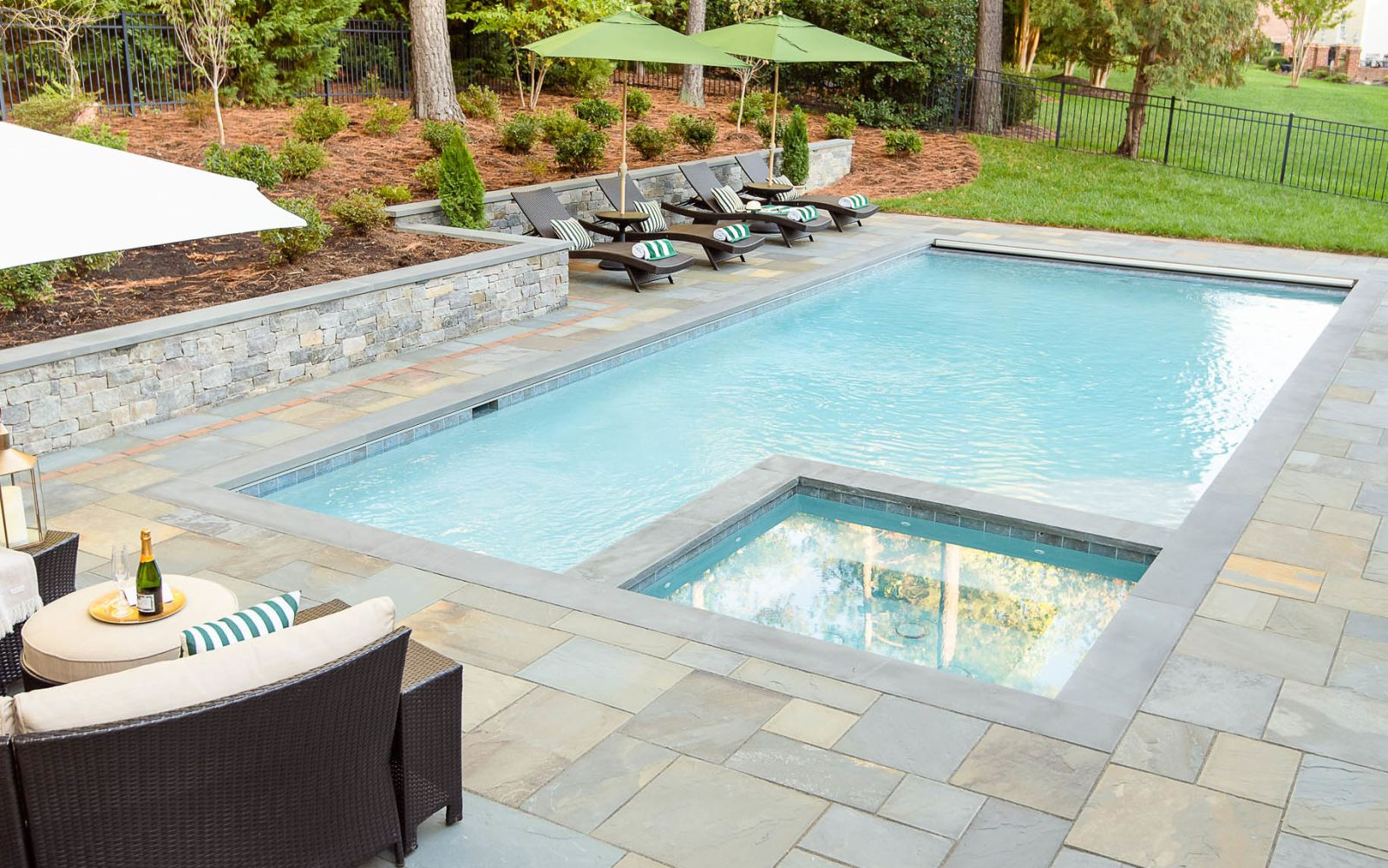 lounge chairs sit alongside the underground pool installed in the backyard with a stone retaining wall separating them from the pine trees
