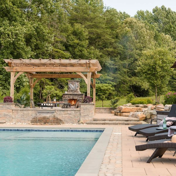 Gunite pool with paver pool decking, fireplace, and pergola
