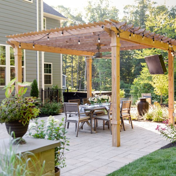 Pergola with outdoor television and bistro lights covering a dining area.
