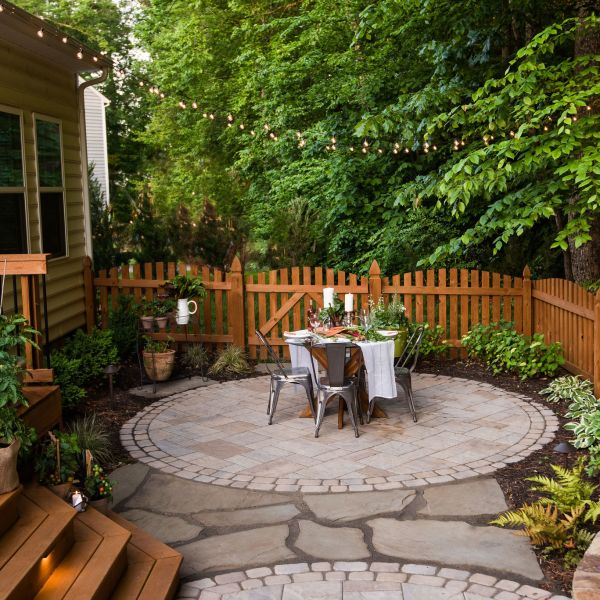 Paver patio with outdoor dining landscaping and string lights