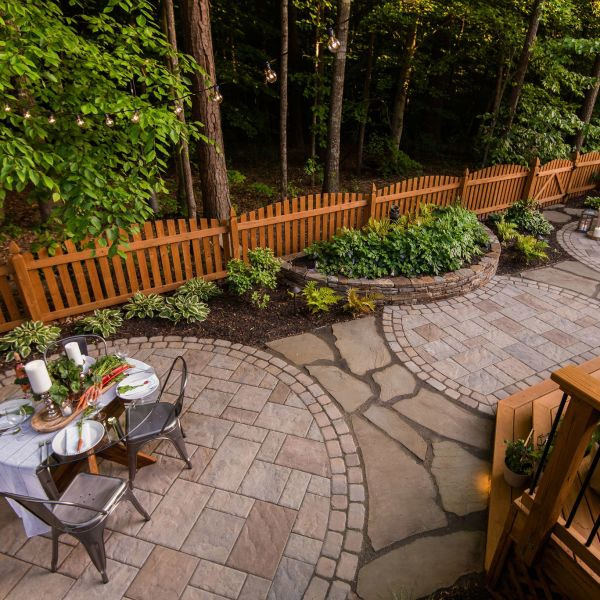 Textured outdoor living space with paver patio, natural stone wall, and landscaping