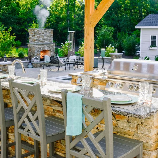 Smoke billowing from outdoor fireplace near outdoor kitchen