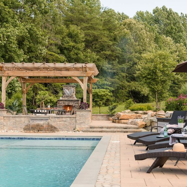 rustic patio, pergola and fireplace installed around the backyard pool