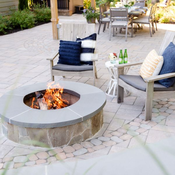 Stone fire pit on a paver patio with two chairs