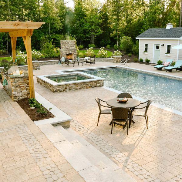 Classic backyard landscaping with a fiberglass pool and hut tub