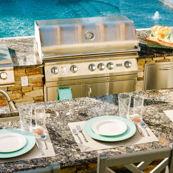 Outdoor grill island with granite countertop and itable