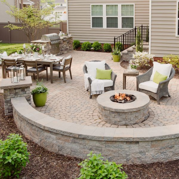 Paver patio with gas fire pit, sitting walls, and grill island.
