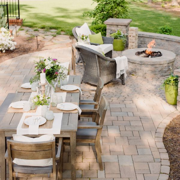 Techo-Bloc paver patio with outdoor dining table, gas fire pit, sitting wall, and pillars.