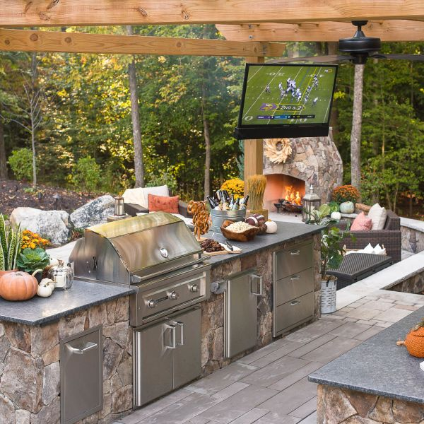 outdoor tv installed over grill island with granite countertops