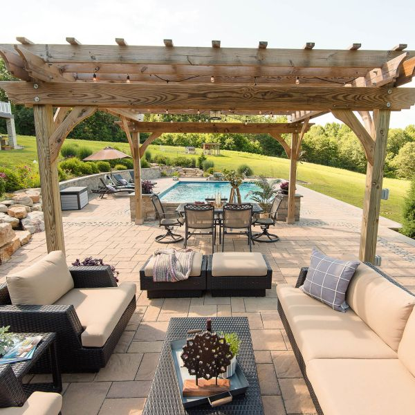 Outdoor sitting area with dark wicker couches and coffee table with tan cushions comfortably placed on natural stone paver patio under a pergola
