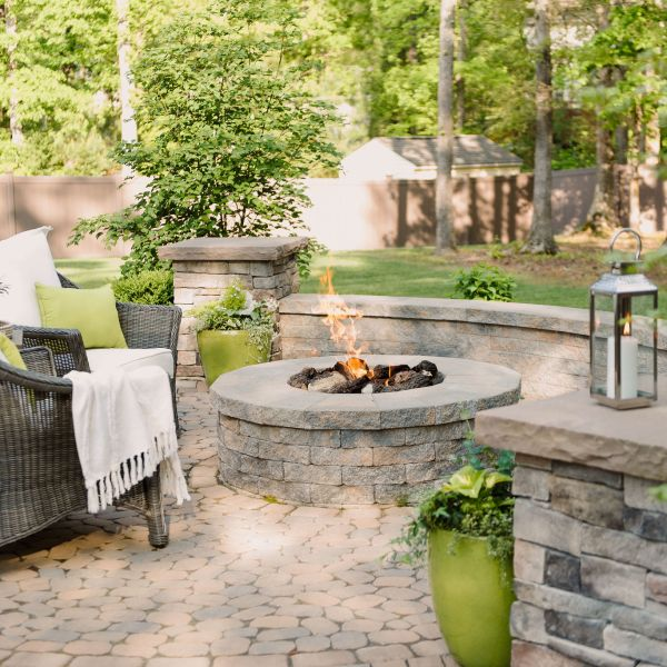Gas fire pit with sitting wall and pillars on a paver patio.