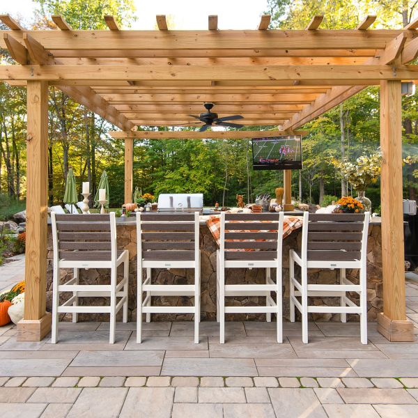 Pergola covered outdoor kitchen with four bar chairs
