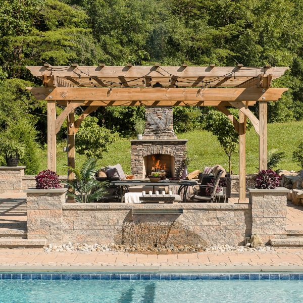 Gunite pool with paver pool decking,outdoor fireplace, wall fountain, and pergola
