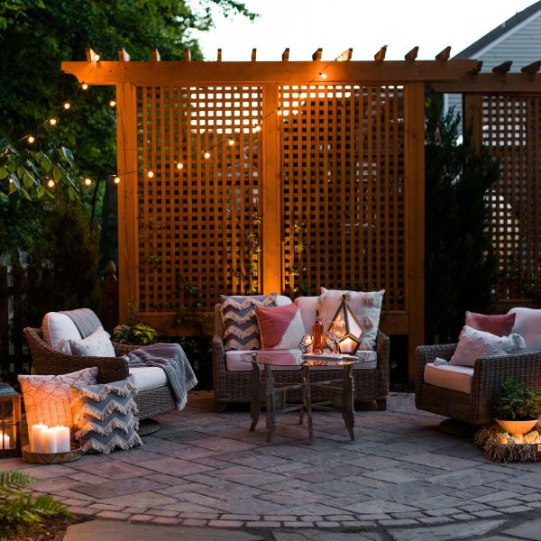 Paver patio with wood trellis privacy screens and string bistro lights