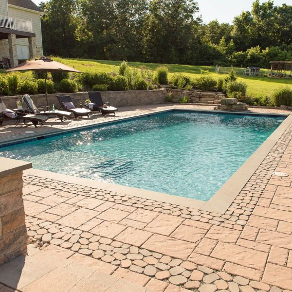 Gunite pool with paver decking and retaining wall