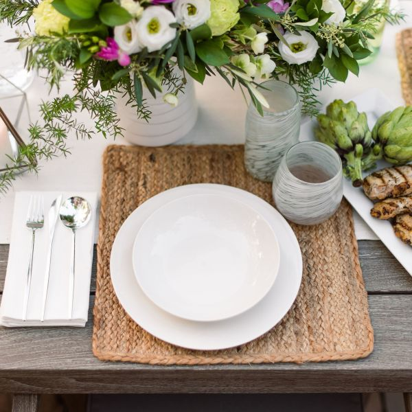 Outdoor dining table setting with grilled chicken.
