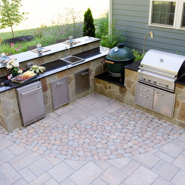 Outdoor kitchen with grill, big green egg smoker, sink, refrigerator and bar top seating