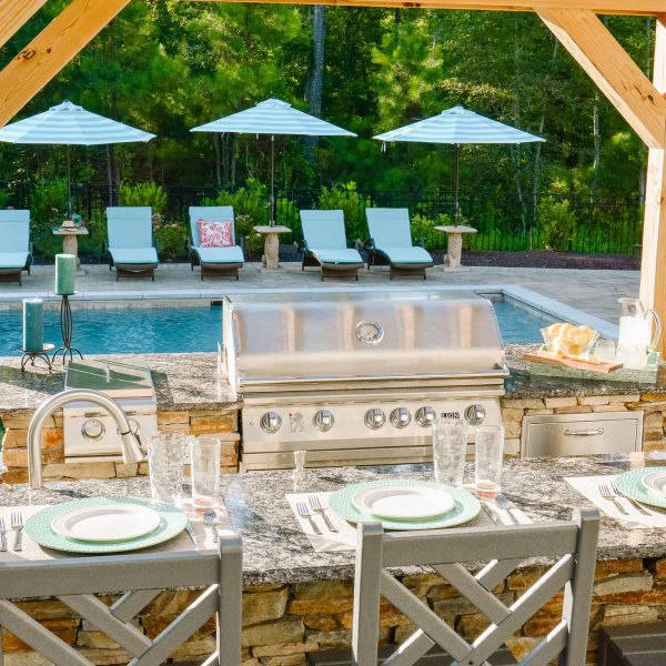 backyard kitchen with granite countertops and steel gas grill