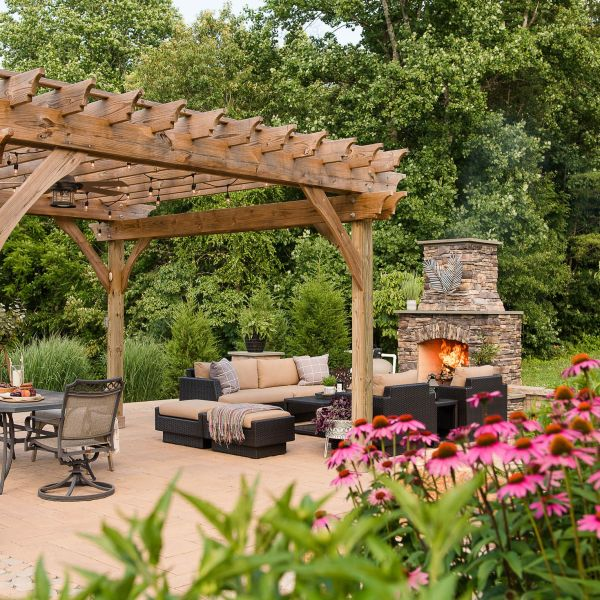 Large pergola covering back patio sitting area with woods in the background