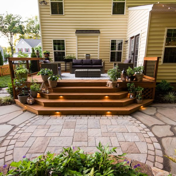 Deck with container gardening and wide steps leading to paver patio