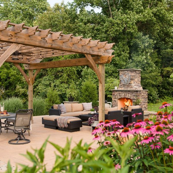 paver patio with pergola, outdoor fireplace, and native landscaping