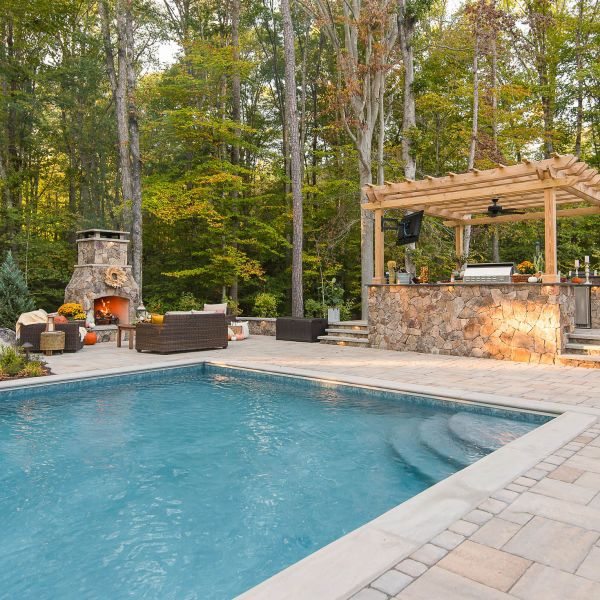 Installed fiberglass pool in backyard patio nearby the fireplace and pergola