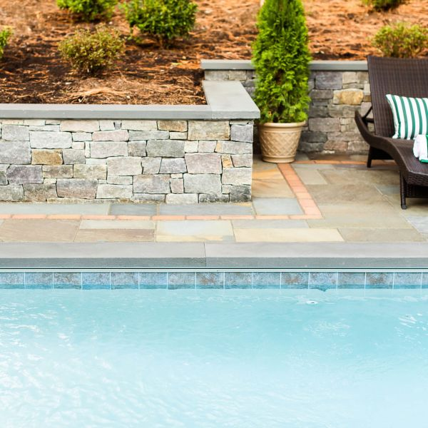 beautifully laid paver patio between retaining wall and underground pool
