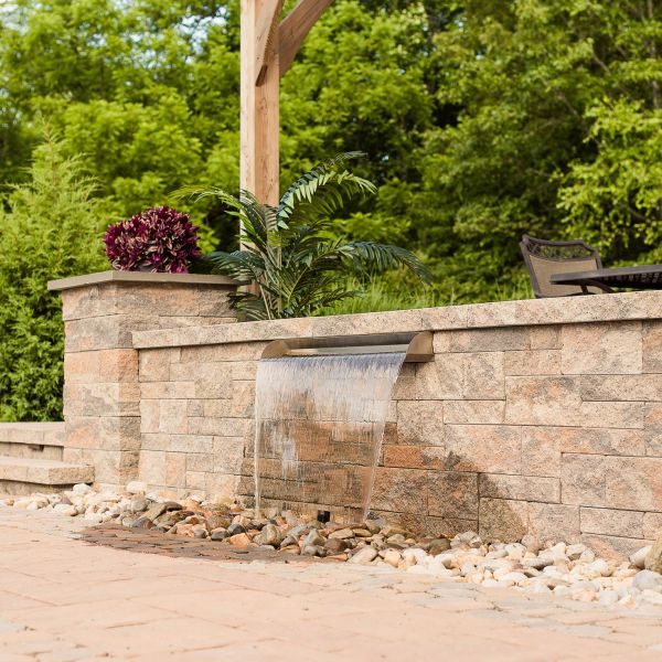 Stone knee wall with a water fountain feature flowing from it