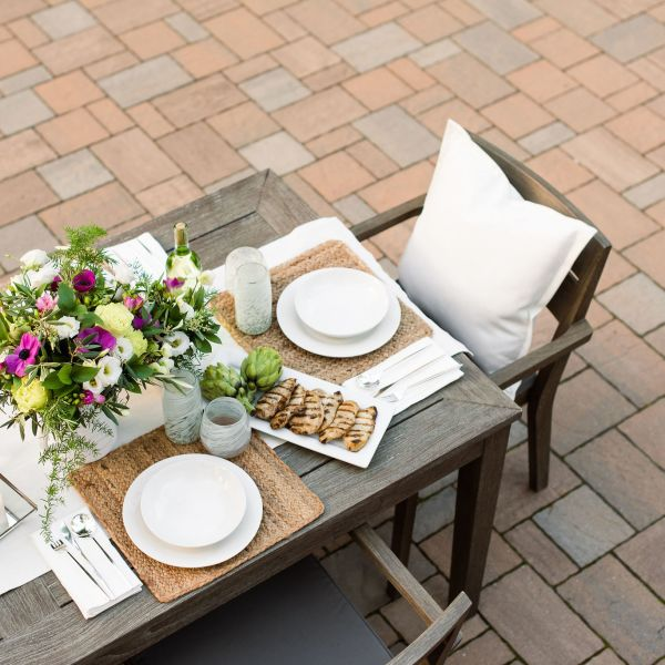 outdoor dining table setting on a Techo-Bloc paver patio.