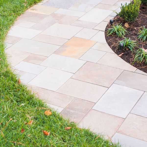 Paver path light-stone hardscape between lawn and landscaped mulched area