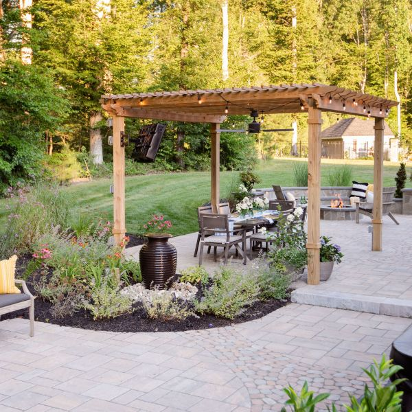 Expansive paver patio with landscaping, bubbling urn, pergola, hot tub, and fire pit.