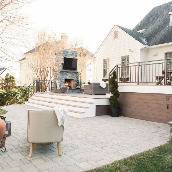 beautiful landscaped backyard with a deck, patio and fireplace