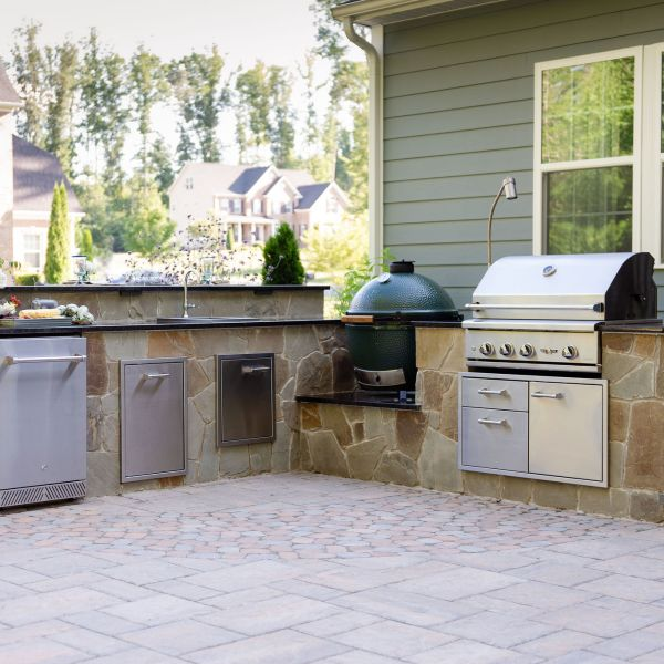 Outdoor kitchen with grill, egg smoker, refrigerator, and bar top seating