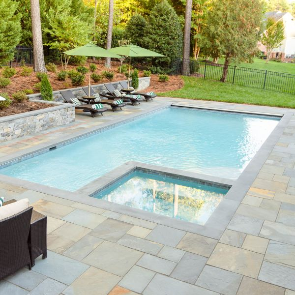 Underground pool installed with one corner of the pool turned into a hot tub