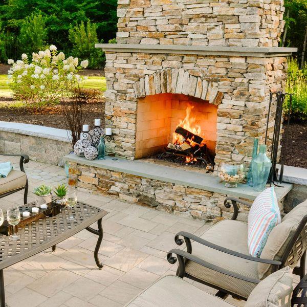 Stacked veneer stone outdoor fireplace on backyard patio