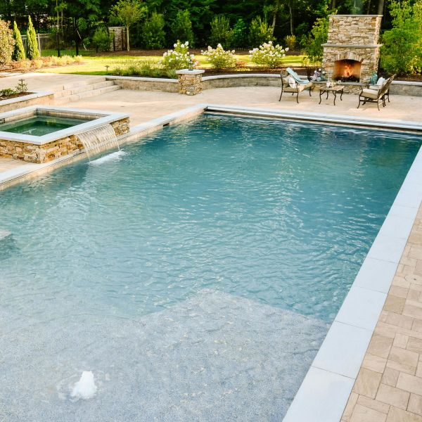Fiberglass underground pool installed by the hot tub and fire place