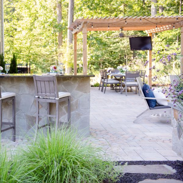 Expansive patio with pergola, outdoor television, bar top seating, outdoor kitchen, fire pit, and landscaping.
