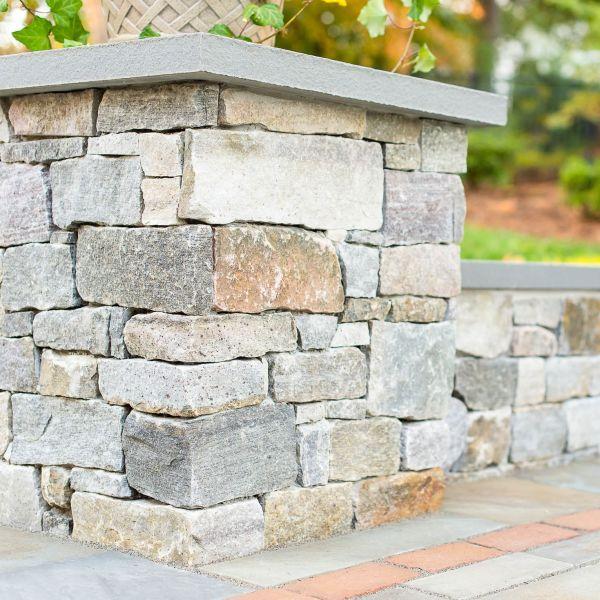 Stacked veneer stone column corner of a sitting wall
