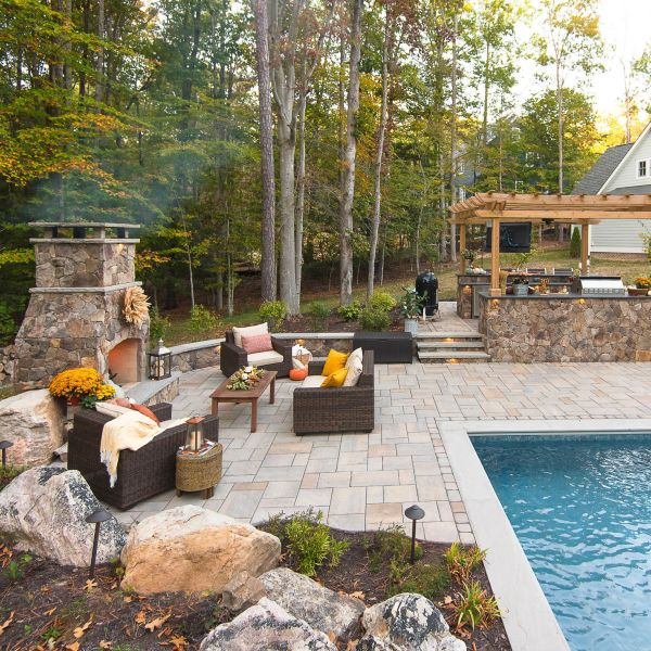 hardscape project with natural stone patio, wood pergola and fiberglass pool