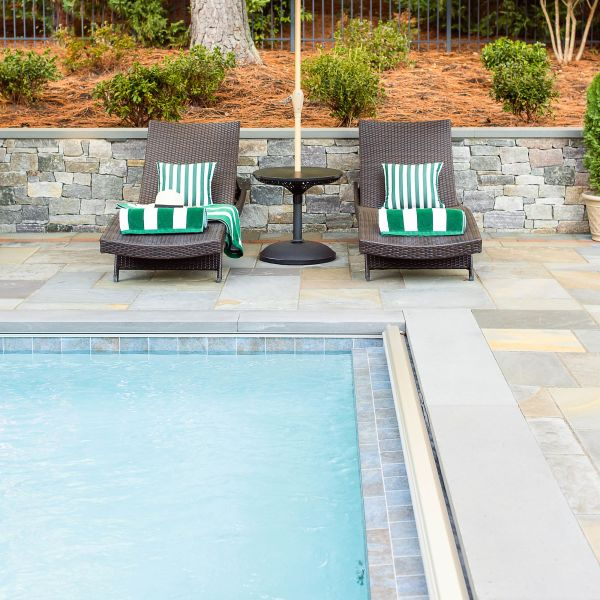 two wicker lounge chairs sit between a sitting wall and underground fiberglass pool
