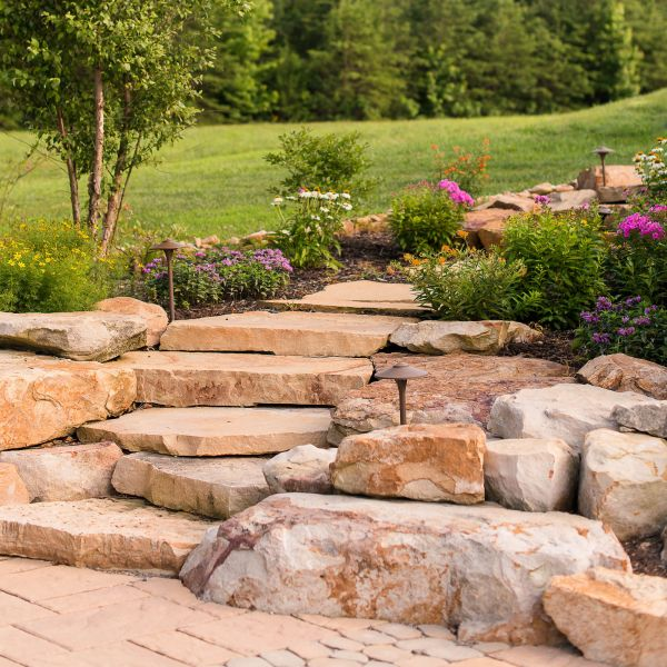 Natural stone steps leading through the backyard with flowers and plants on either side