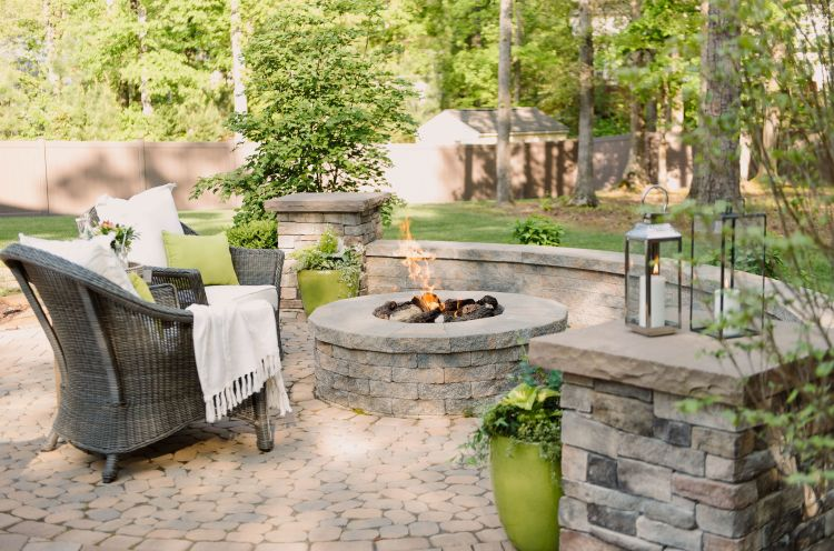 Landscaped backyard with pavers built around a fire pit
