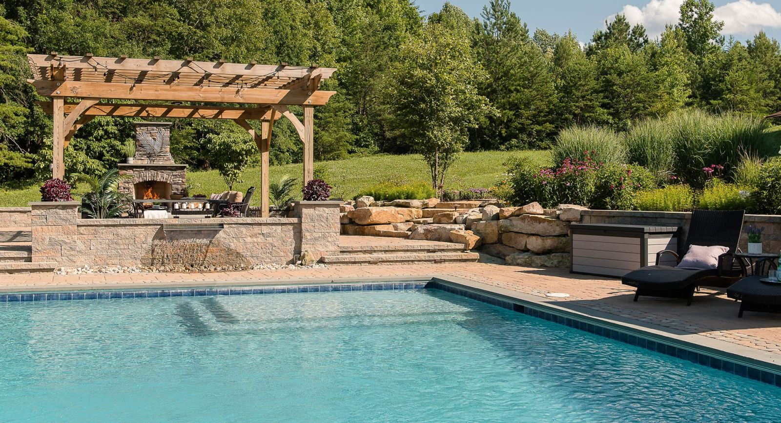 Luxury backyard pool surrounded by red brick paver patio and longe chairs, fire place and pergola