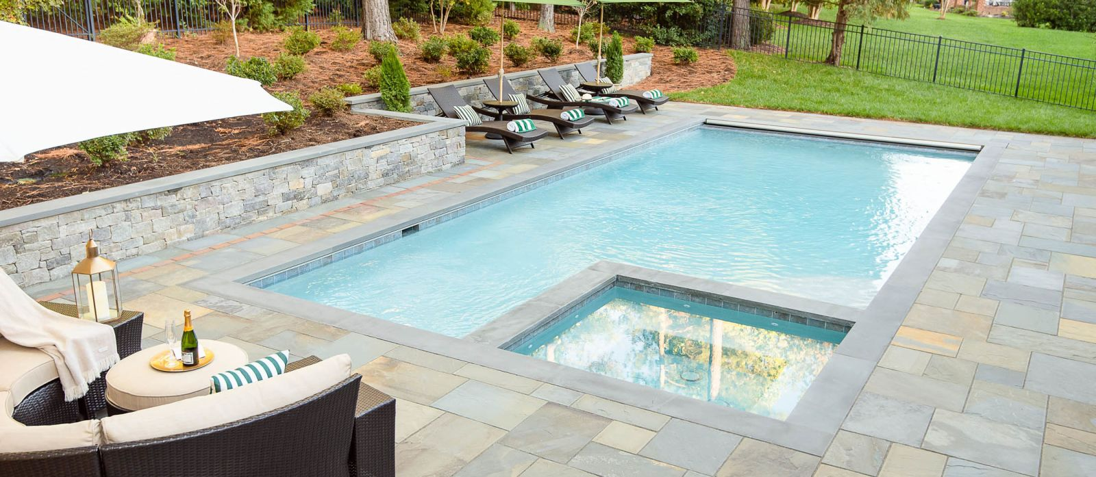 Newly installed backyard pool and hot tub with retaining wall