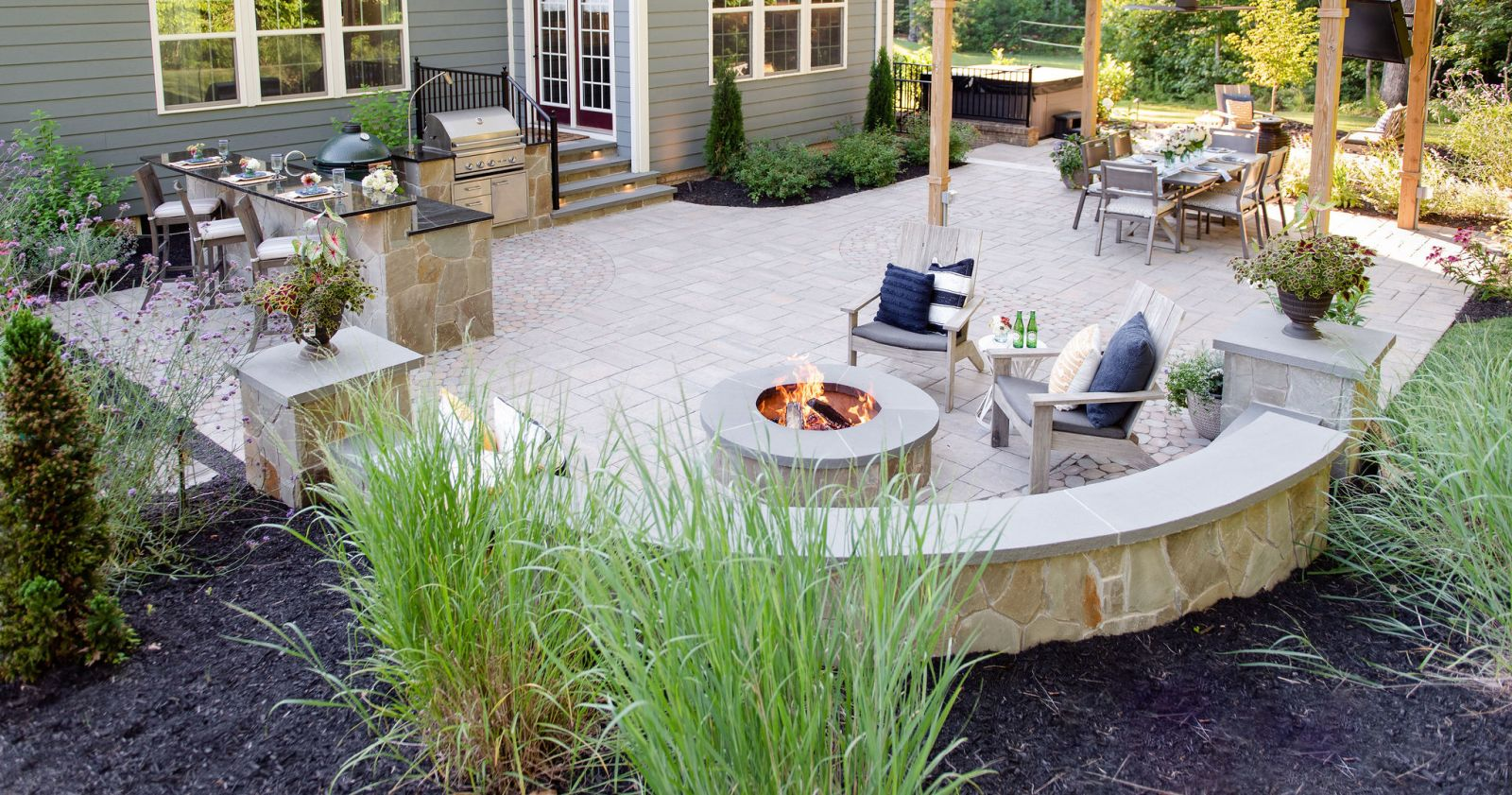 Expansive paver patio with fire pit, pergola, outdoor kitchen, and hot tub.