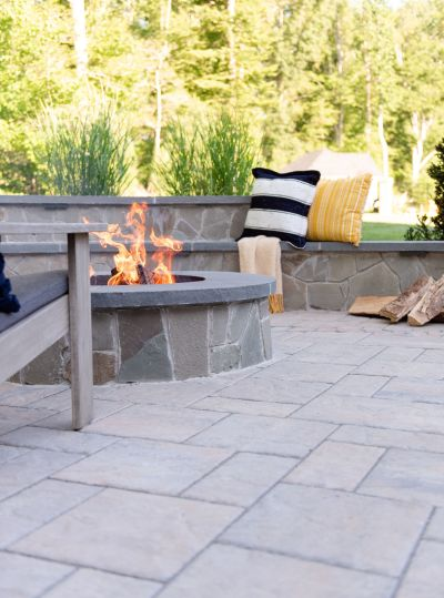 Stone fire pit on a paver patio with sitting wall