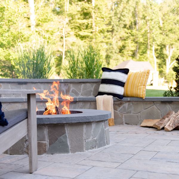 Stone, wood burning fire pit with bench-style sitting wall